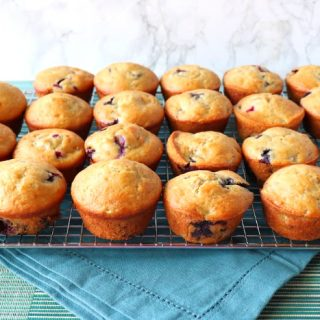 Cooling rack loaded with blueberry muffins and a blue napkin