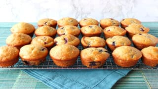 Two dozen Blueberry Banana Muffins lined up on a cooling rack with a blue napkin underneath.