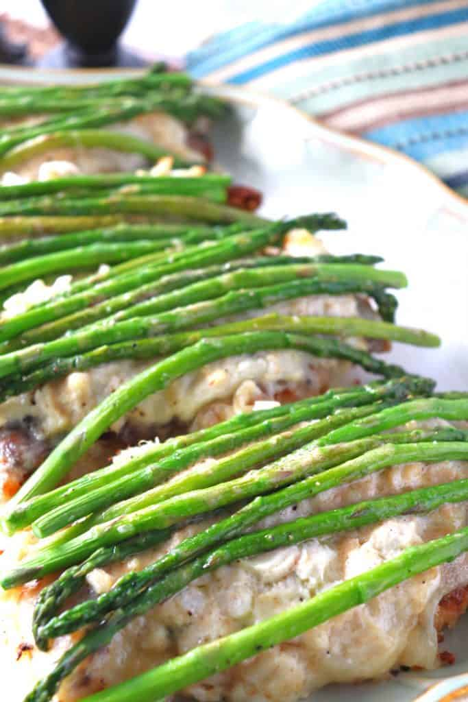Vertical image of chicken Oscar with fresh asparagus spears over top