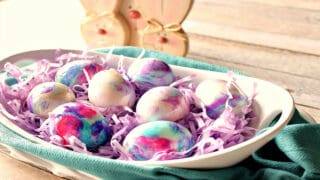 An oval white bowl filled with pastel colored Tie-Dye Easter Eggs.