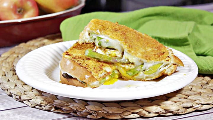 A Breakfast Grilled Cheese Sandwich on a white plate with a green napkin in the background.