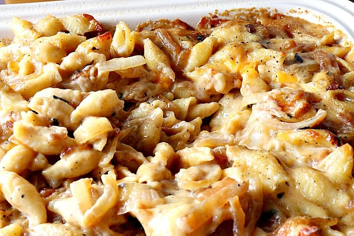 Closeup photo of cheesy shells and cheese with caramelized onions.