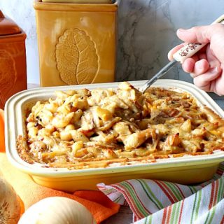 Hand with a spoon serving up French onion mac and cheese out of a casserole dish.