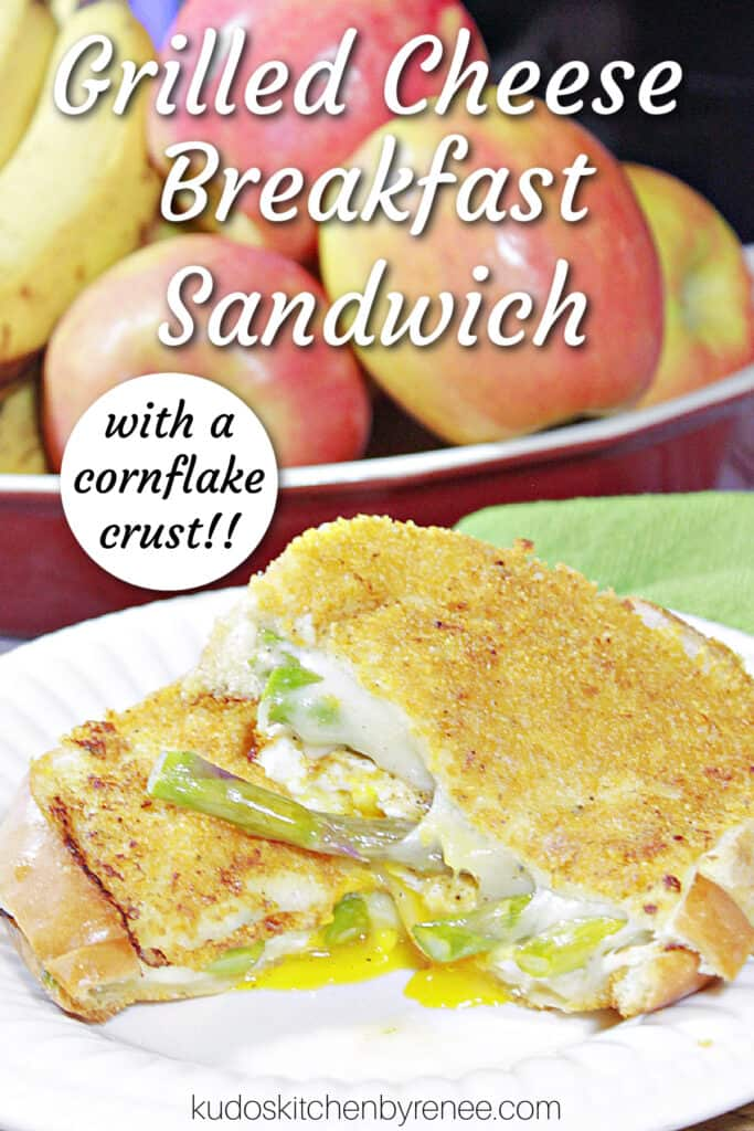 A vertical closeup of a sliced Grilled Cheese Breakfast Sandwich with a cornflake crust and a title text overlay graphic.