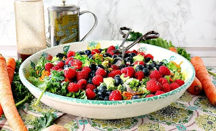 Large bowl with a kale salad with blueberries, raspberries, and blackberries.