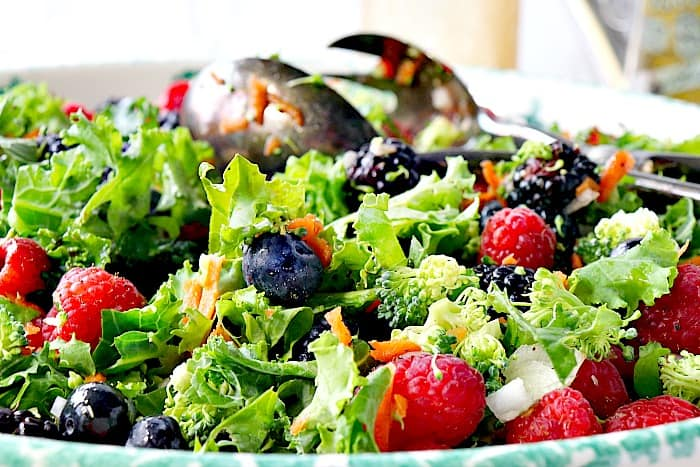 Closeup photo of a kale salad in a bowl with raspberries, blueberries, blackberries, and tongs.