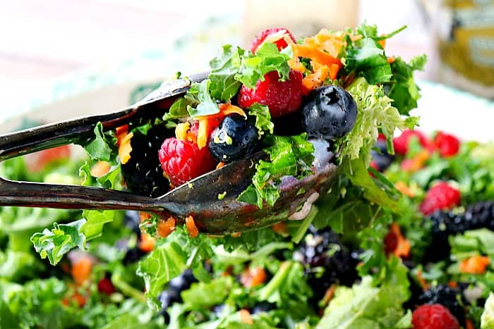 Closeup photo of salad tongs holding a kale, blueberries, raspberries, and blackberries salad over a salad bowl.