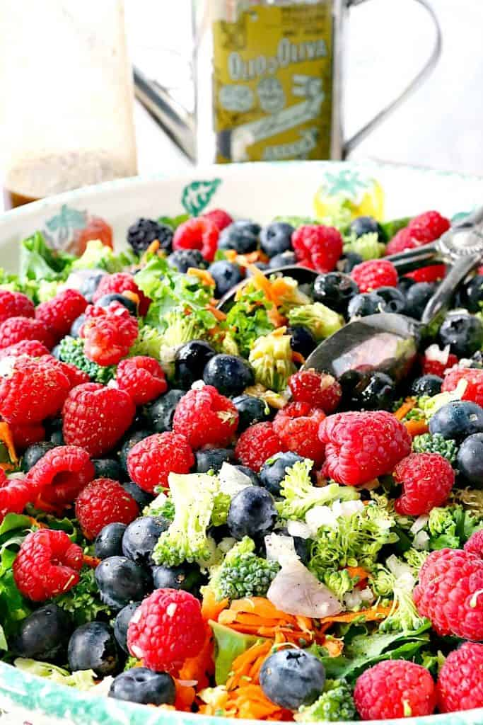 Vertical image of a kale salad with tongs, raspberries, blueberries, shredded carrots, and broccoli with a tin of olive oil in the background.
