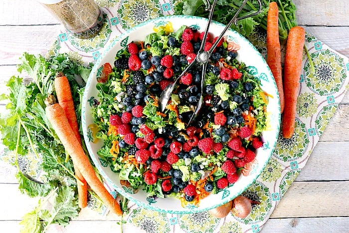 Overhead photo of a large bowl of colorful kale salad with carrots, kale, and shallots surrounding the bowl as accents. Healthy Salad Recipe Roundup.
