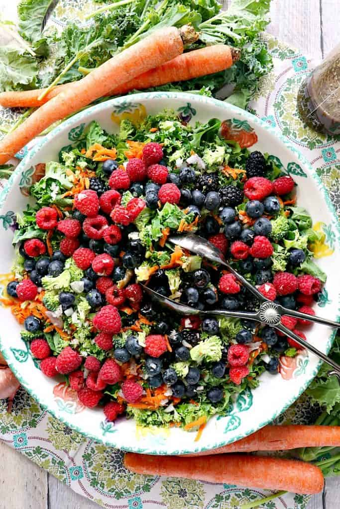 Overhead vertical photo of a giant bowl filled with kale and berry salad with blueberries, raspberries, carrots, kale, and salad tongs.