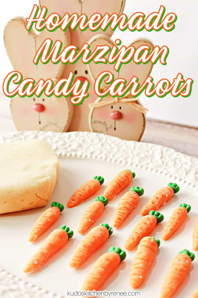 A vertical closeup image of a bunch of Homemade Marzipan Candy Carrots on a platter with a block of homemade marzipan in the background.
