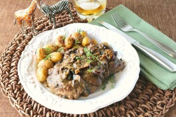 Steak with bourbon mushroom sauce on a white plate with baby potatoes and fresh herbs.