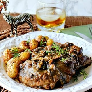 Steak with Bourbon Mushroom Sauce on a white plate with a glass of bourbon with ice in the background.