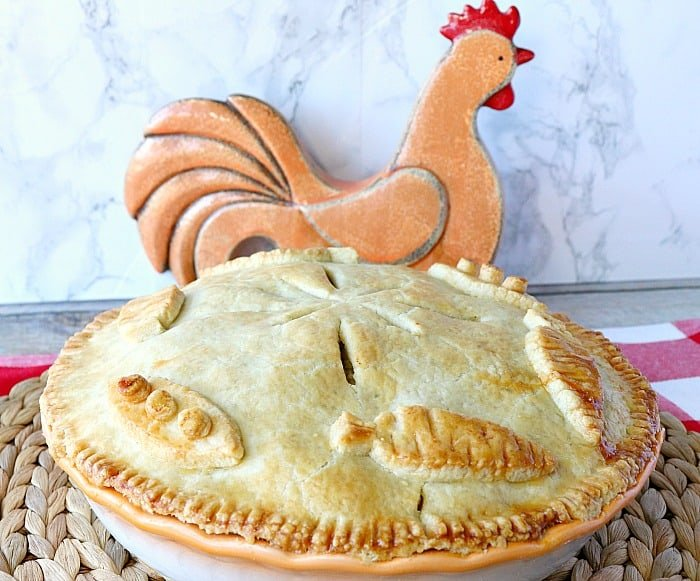 Chicken and Rice Pot Pie on a woven place mat with a ceramic chicken in the background and a red and white check tablecloth.