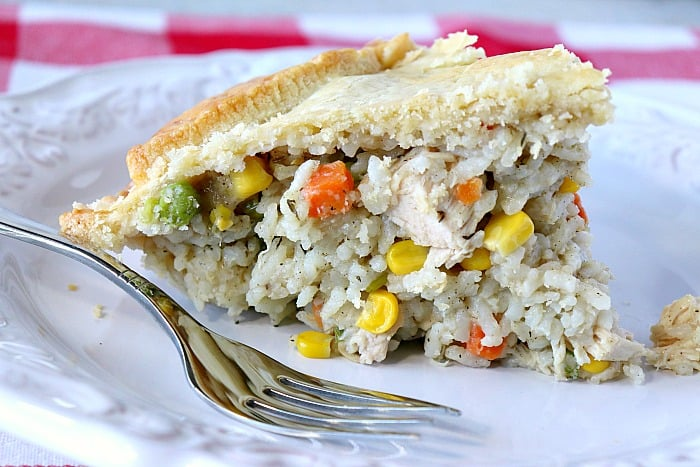A slice of a savory chicken pot pie on a white plate with a fork.