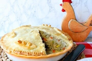Chicken pot pie with rice and vegetables with a slice taken out.
