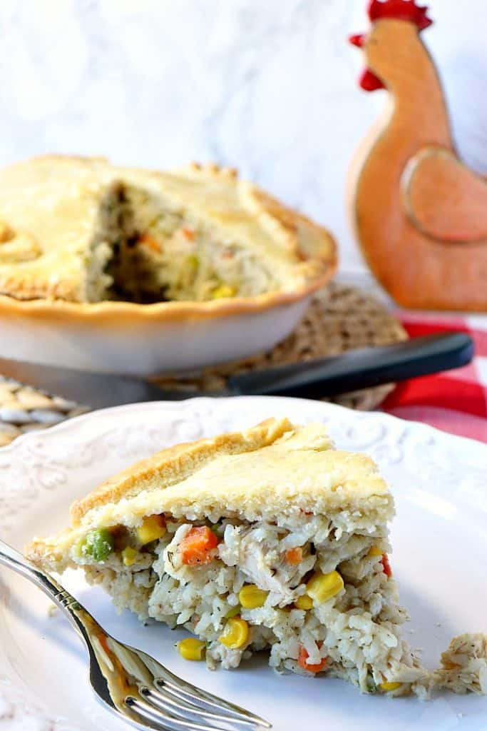 A slice of chicken and rice pot pie in the foreground and a whole pie in the background.