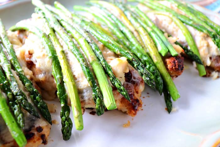 Closeup picture of breaded chicken breasts with Swiss cheese, crabmeat, and fresh asparagus spears.