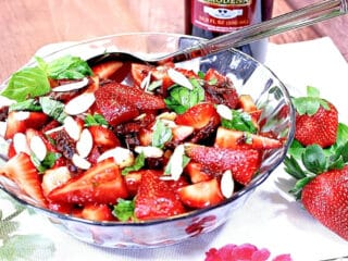 A red, green, and white Strawberry Basil Salad in a glass bowl with basil, almonds, and sun dried tomatoes.