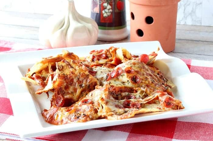 A pile of pepperoni pizza nachos on a white plate with a red and white check tablecloth.