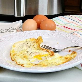 Fried eggs on a white plate with a fork and an air fryer in the background