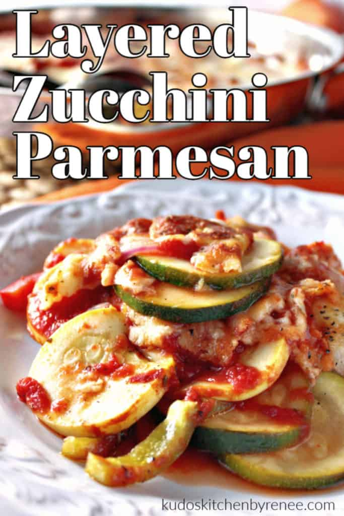 Vertical closeup image of zucchini and summer squash with tomato sauce and parmesan cheese on a white plate.