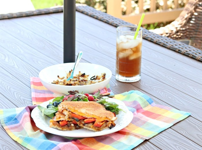 A grilled cheese sandwich on a picnic table with a glass of iced tea and colorful napkin.