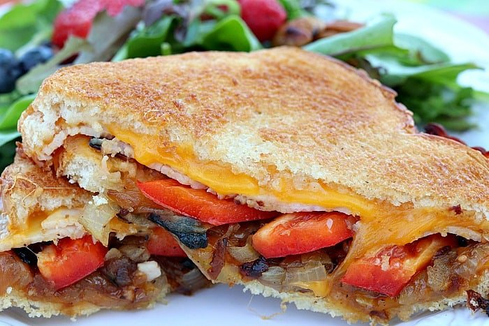 closeup photo of a grilled cheese sandwich cut in half with caramelized onions and red bell pepper.