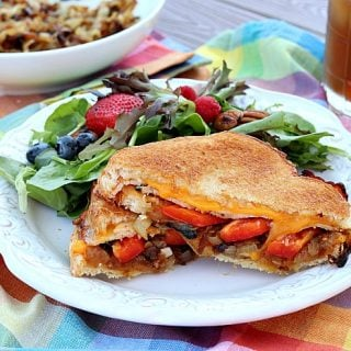 Grilled cheese sandwich with red bell pepper on a picking table with a salad on a plate.