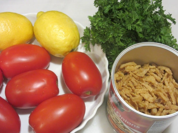 Plum tomatoes and lemons in a dish with French fried onions and parsley on the side.