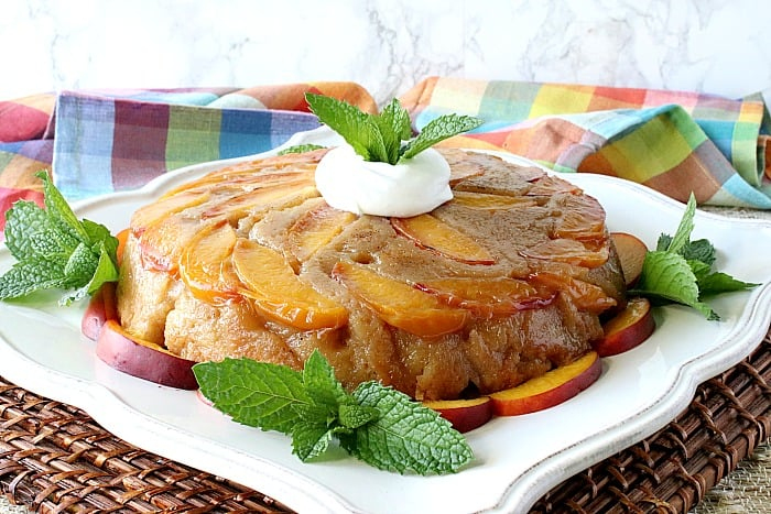 A whole nectarine upside down cake on a square white plate with mint sprigs and a dollop of whipped cream.