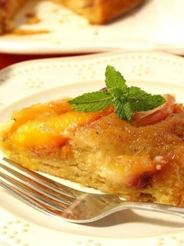 A slice of nectarine upside down cake on a white plate with a fork and a sprig of mint for garnish