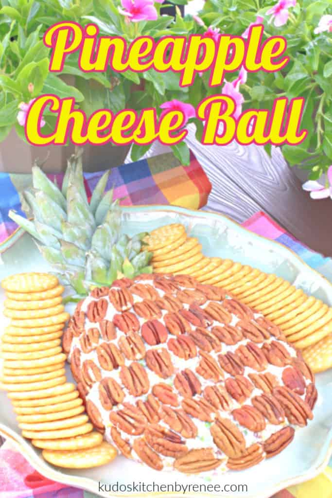 A pineapple cheese ball with crackers on the side and flowers in the background with a title text overlay graphic