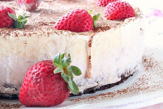 Drip running down the side of a Neapolitan ice cream cake with strawberries.
