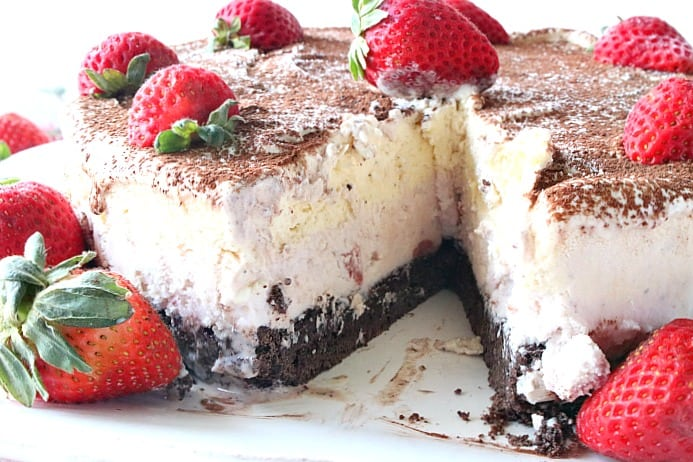 A Neapolitan Ice Cream Cake on a plate with a slice taken out and a strawberry garnish.
