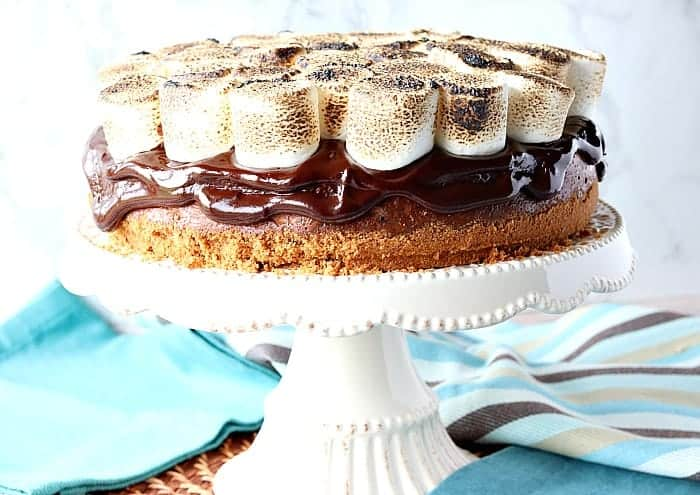 S'mores cheesecake on a cake stand with blue napkins in the background. Romantic chocolate dessert recipes collection.