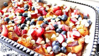 A casserole dish filled with Red, White, and Blue Bread Pudding with berries and white chocolate chips.