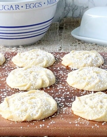 Rows of Viennese Whirls cookies on a wooden tray and powdered sugar dusting