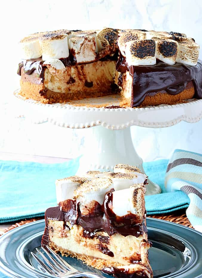 A slice of chocolate chip s'mores cheesecake on a plate with a cake stand with the cheesecake in the background.