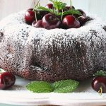 A chocolate bundt cake on a white plate with cherries and mint.