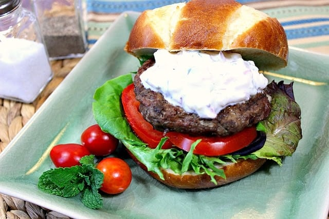 Horizontal photo of a Greek lamb burger on a square aqua color plate with tzatziki sauce and tomatoes.