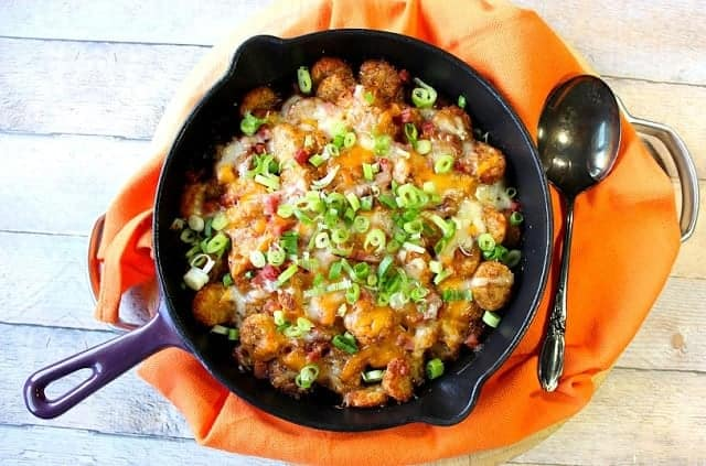 Overhead photo of a skillet filled with tater tot poutine.