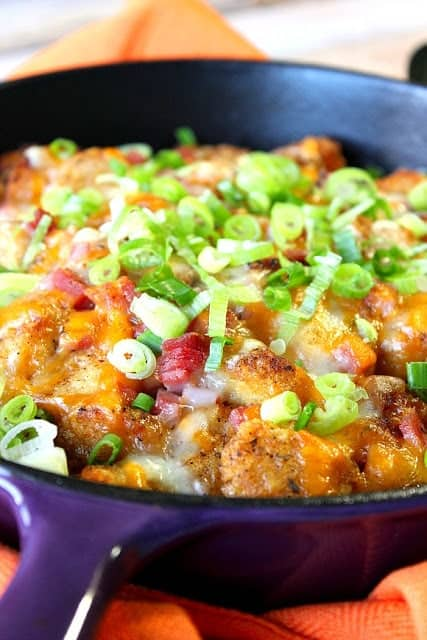 Closeup vertical image of tater tot poutine with melted cheese, ham, and green onion.