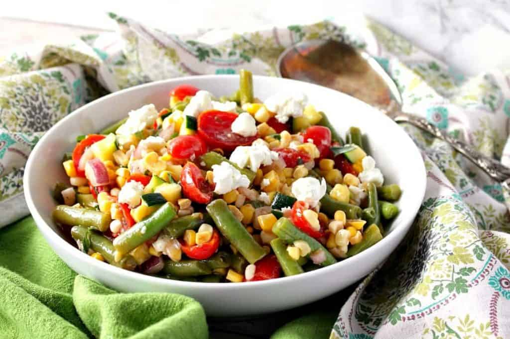 White bowl filled with Farmer's Market Veggie Salad with green beans, corn, tomatoes, and goat cheese.