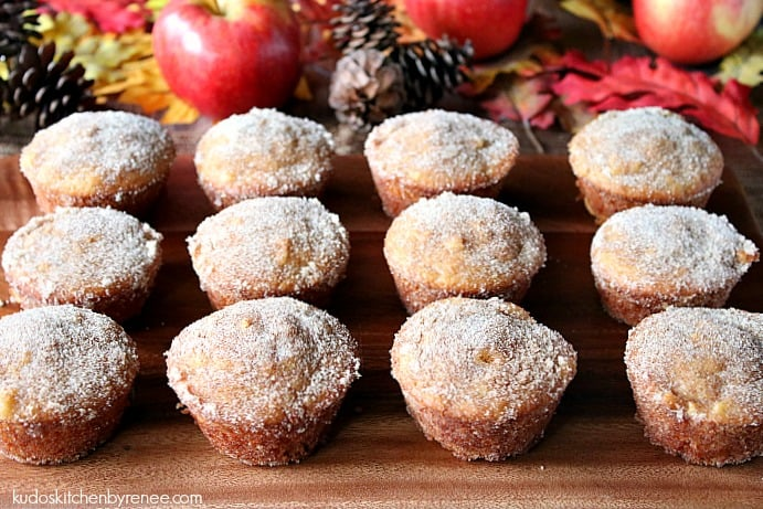 One dozen apple cider donut muffins on a wooden board with apples and autumn leaves in the background.