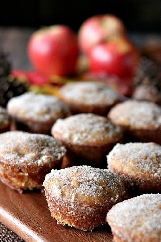 Vertical photo of apple cider donut muffins with cinnamon sugar coating and apples in the background.