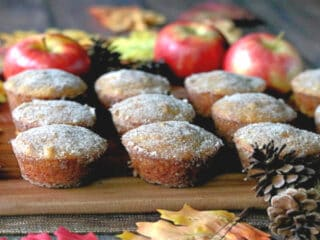 Apple Cider Donuts On A Wood Tray With Apples And Pine Cones