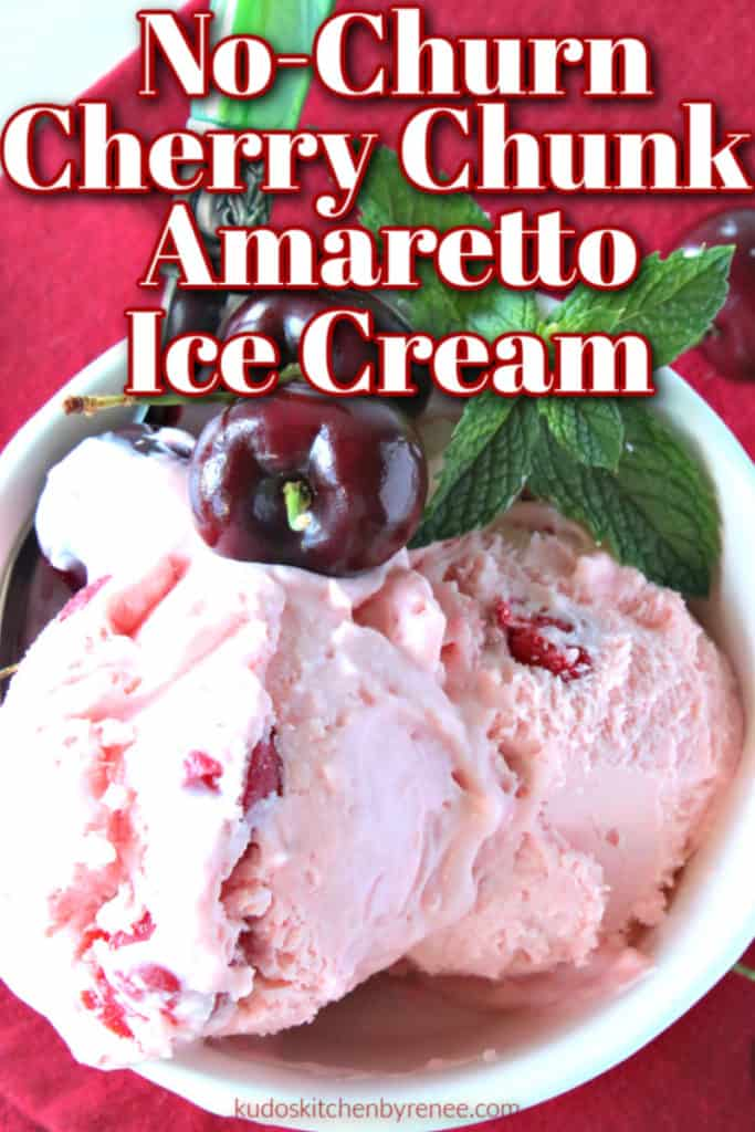 Closeup vertical photo of a dish of no-churn cherry chunk amaretto ice cream with mint leaves and fresh cherries.
