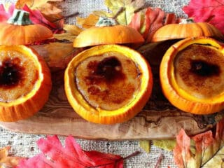Overhead photo of three pumpkin creme brulee on a wooden board with autumn leaves all around.