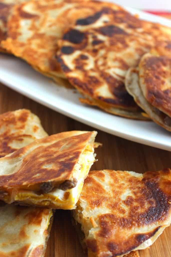 Closeup vertical photo of a breakfast quesadilla with sausage, egg, and cheese on a white platter.